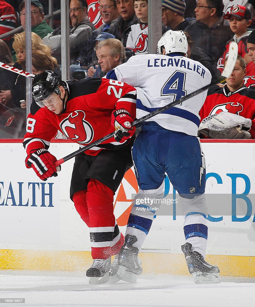 Vincent Lecavalier #4 of the Tampa Bay Lightning and Anton Volchenkov #28 of the New Jersey Devils come together during the game at the Prudential Center on February 7, 2013 in Newark, New Jersey.