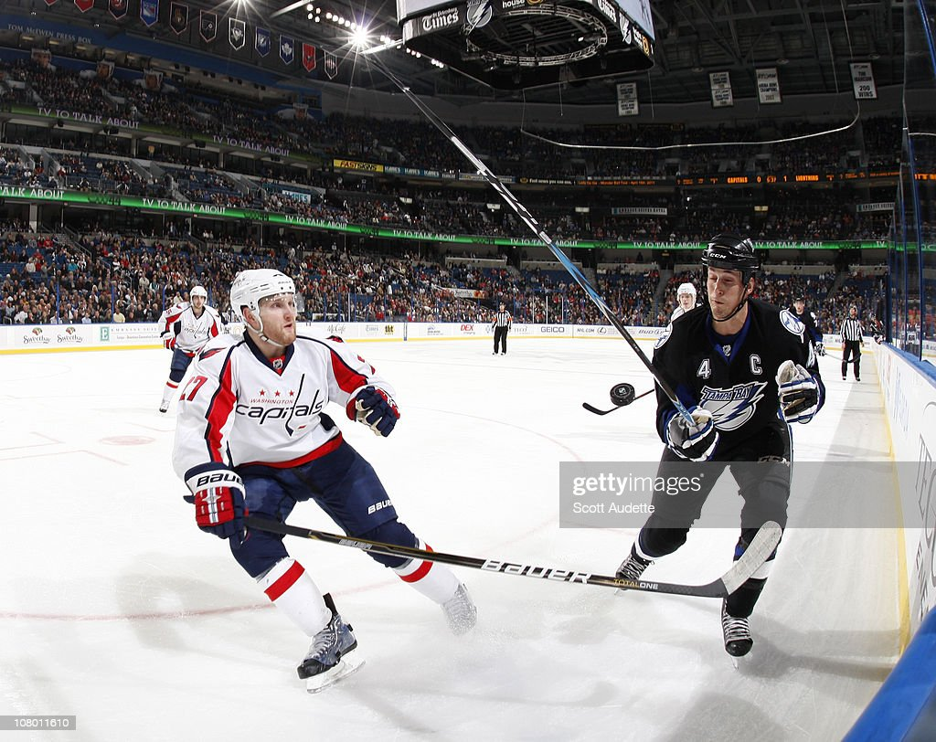 <a gi-track='captionPersonalityLinkClicked' href=/galleries/search?phrase=Vincent+Lecavalier&family=editorial&specificpeople=201915 ng-click='$event.stopPropagation()'>Vincent Lecavalier</a> #4 of the Tampa Bay Lightning blocks the puck as <a gi-track='captionPersonalityLinkClicked' href=/galleries/search?phrase=Karl+Alzner&family=editorial&specificpeople=3938829 ng-click='$event.stopPropagation()'>Karl Alzner</a> #27 of the Washington Capitals tries to clear it out of the zone during the first period at the St. Pete Times Forum on January 12, 2011 in Tampa, Florida.