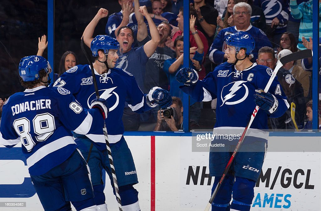 Vincent Lecavalier #4 of the Tampa Bay Lightning celebrates a goal with teammates <a gi-track='captionPersonalityLinkClicked' href=/galleries/search?phrase=Benoit+Pouliot&family=editorial&specificpeople=879830 ng-click='$event.stopPropagation()'>Benoit Pouliot</a> #67 and Cory Conacher #89 during the third quarter of the Tampa Bay Lightning against the Florida Panthers at the Tampa Bay Times Forum on January 29, 2013 in Tampa, Florida.