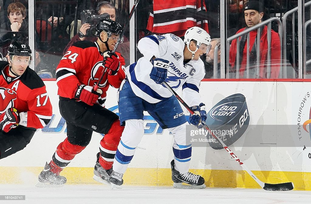 Vincent Lecavalier #4 of the Tampa Bay Lightning in action against Bryce Salvador #24 of the New Jersey Devils at the Prudential Center on February 7, 2013 in Newark, New Jersey. The Devils defeated the Lightning 4-2.