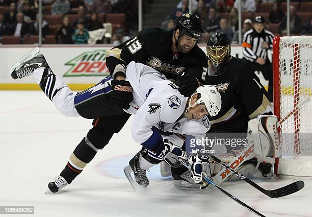 Vincent Lecavalier of the Tampa Bay Lightning is taken down by Paul Mara of the Anaheim Ducks as goaltender Jonas Hiller of the Ducks defends in the...