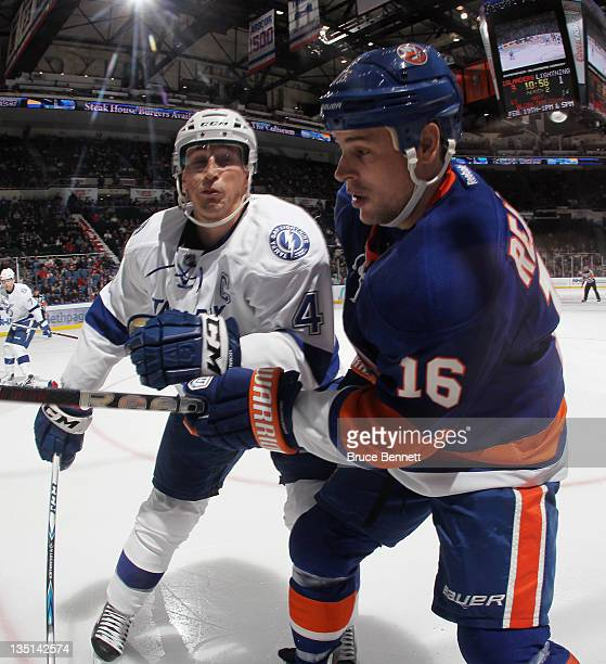 Vincent Lecavalier of the Tampa Bay Lightning moves in to check Marty Reasoner of the New York Islanders at the Nassau Veterans Memorial Coliseum on...