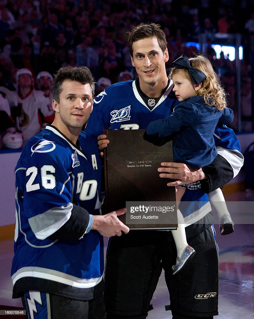 Vincent Lecavalier #4 of the Tampa Bay Lightning receives a gift from fellow teammate, Martin St. Louis #26, during his 1,000th NHL game ceremony prior to tonights game against the Ottawa Senators at the Tampa Bay Times Forum on January 25, 2013 in Tampa, Florida.