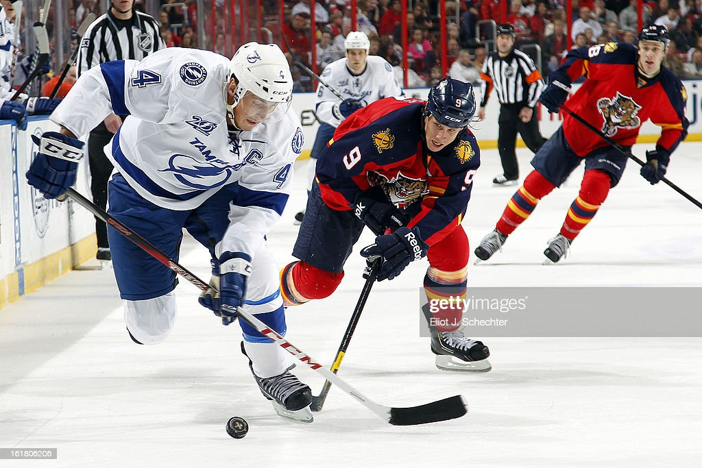 Vincent Lecavalier #4 of the Tampa Bay Lightning skates with the puck against Stephen Weiss #9 of the Florida Panthers at the BB&T Center on February 16, 2013 in Sunrise, Florida.