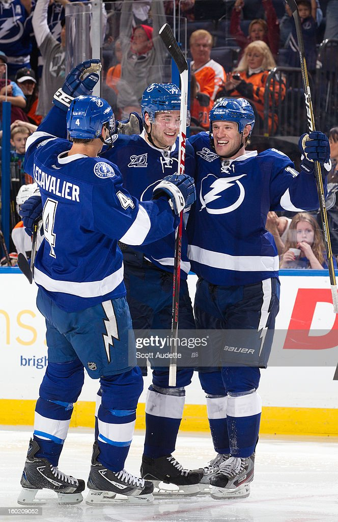 Vincent Lecavalier #4, Victor Hedman #77 and Adam Hall #18 of the Tampa Bay Lightning celebrate after scoring during the third period of a Tampa Bay Lightning game against the Philadelphia Flyers at the Tampa Bay Times Forum on January 27, 2013 in Tampa, Florida.