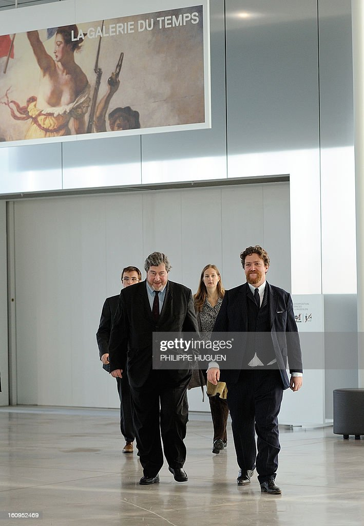 Vincent Pomarede (L), curator of the exhibition of the Louvre-Lens Museum, and Director of the Louvre-Lens Museum, Xavier Dectot (R), arrive to speak to journalists on February 8, 2013 in the French northern city of Lens, after a woman vandalized on the eve the Eugene Delacroix masterpiece 'La Liberté guidant le Peuple' (Liberty leading the people, by writing on it 'AE911' with a black permanent marker on the painting.