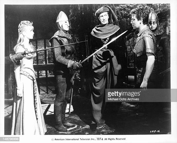 Vincent Price and Jane Asher watching actor David Weston who is held at swordpoint in a scene from the film 'The Masque of the Red Death' 1964