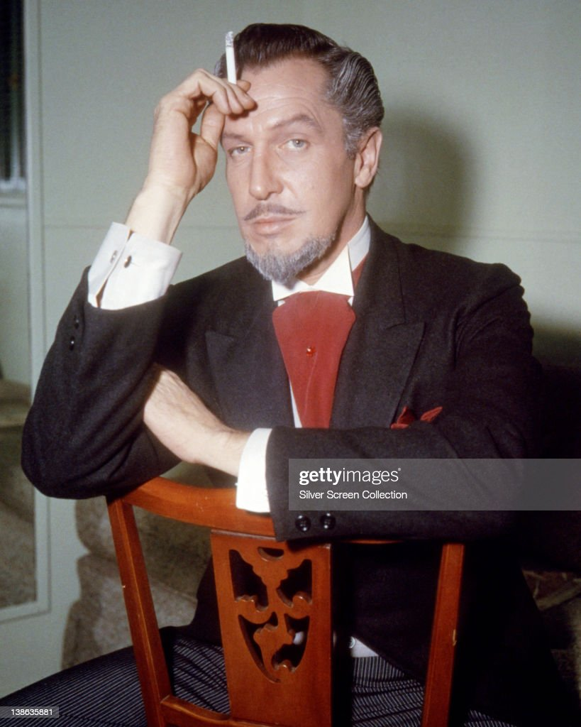 Vincent Price (1911-1993), US actor, with a grey goatee beard, wearing a black jacket with a white shirt and a red cravat, with a red handkerchief in the breast pocket of the jacket, sitting on a chair, circa 1955.