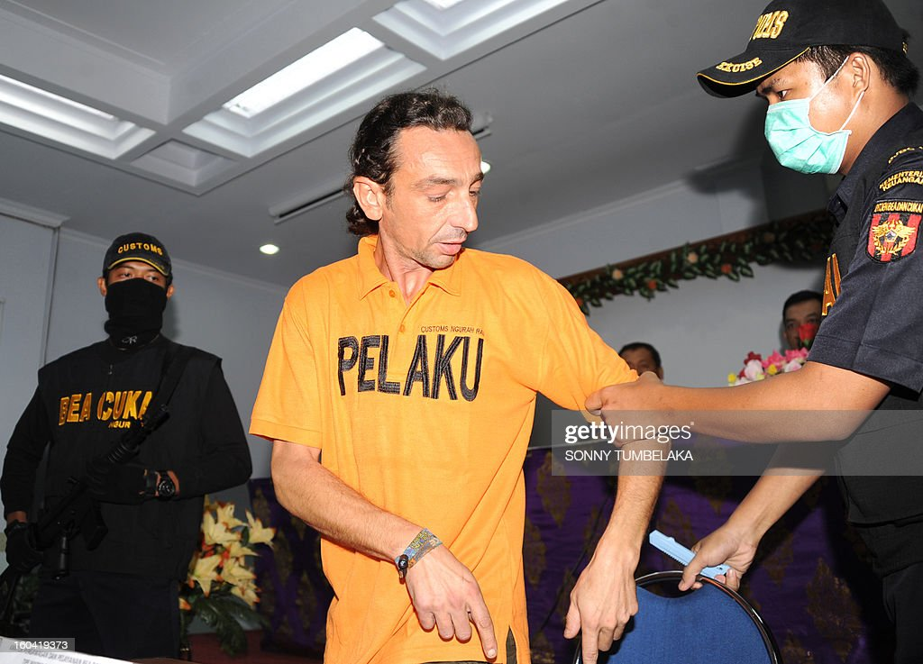 Vincent Roger Petrone of France (C) is escorted by customs security before a press conference at a customs office in Denpasar on Bali island on January 31, 2013. Petrone was arrested at Bali airport on January 29 for allegedly carrying four capsules of hashish, weighing 70 grams, at Bali International Airport in Indonesia, having arrived from Kuala Lumper. If convicted of smuggling the drugs into Indonesia, Petrone could face the death penalty, officials said. AFP PHOTO / SONNY TUMBELAKA