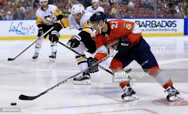 Vincent Trocheck of the Florida Panthers and Brian Dumoulin of the Pittsburgh Penguins fight for the puck during a game at BBT Center on October 20...