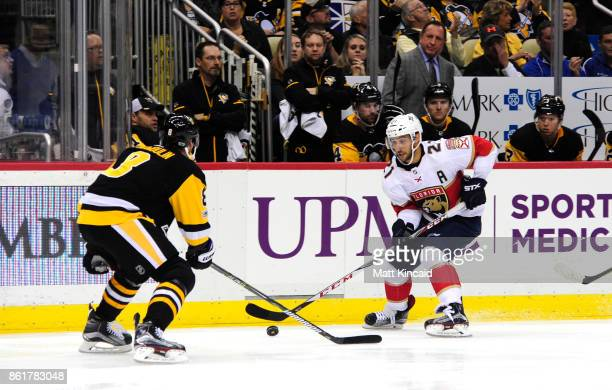 Vincent Trocheck of the Florida Panthers skates with the puck against Brian Dumoulin of the Pittsburgh Penguins at PPG PAINTS Arena on October 14...