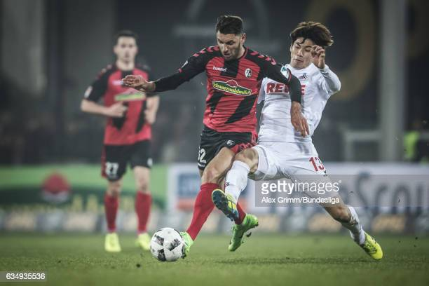 Vincenzo Grifo of Freiburg is challenged by Yuya Osako of Koeln during the Bundesliga match between SC Freiburg and 1 FC Koeln at SchwarzwaldStadion...