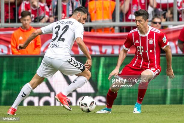 Vincenzo Grifo of SC Freiburg and Robert Lewandowski of FC Bayern Muenchen battle for the ball during the Bundesliga match between Bayern Muenchen...