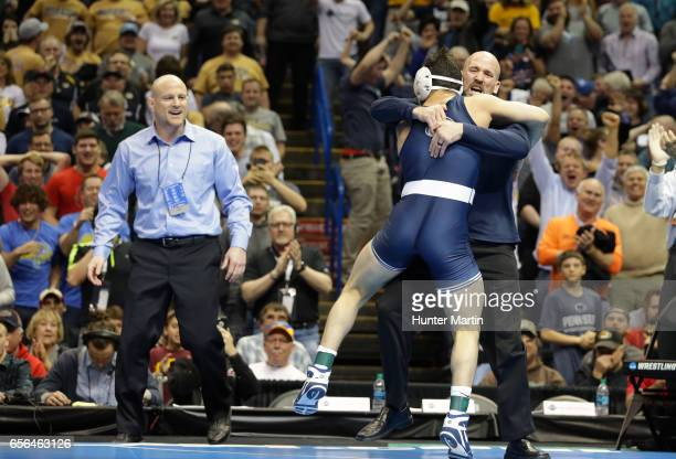 Vincenzo Joseph of the Penn State Nittany Lions jumps into the arms of assistant coach Casey Cunningham as head coach Cael Sanderson looks on after...