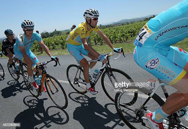 Vincenzo Nibali of Italy and the Astana Pro Team in the overall leader's yellow jersey rides in the protection of teammtes Jakob Fuglsang of Denmark...