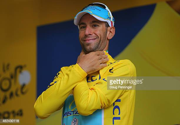 Vincenzo Nibali of Italy and the Astana Pro Team takes the podium after defending the overall race leader's yellow jersey during the fifteenth stage...