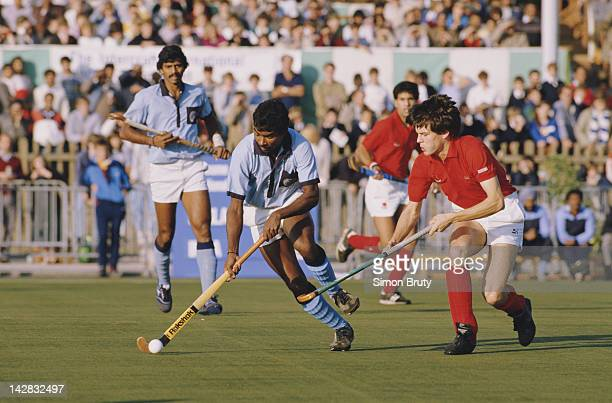 Vineet Kumar Sharma of India fends off a tackle by John Shaw of England during their international match on 6th October 1985 at the National Hockey...
