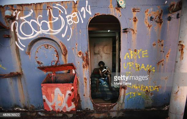 Vinicius who is homeless poses with his cat Nega on his bed where he sleeps on an abandoned ship floating on the polluted Guanabara Bay the Rio 2016...