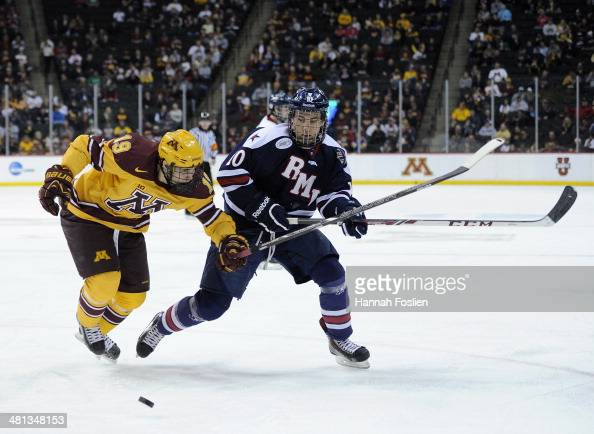 Vinni Lettieri of the Minnesota Golden Gophers and Tyson Wilson of the Robert Morris Colonials skate after the puck during the second period of the...