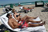 Vinnie Miliano and Erin McGrath spend a day at the beach after their return flight to New York was delayed until Thursday after most Northeast coast...