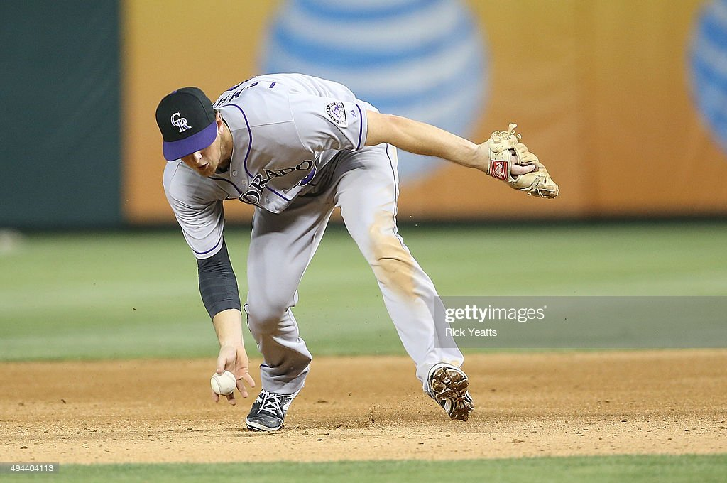 Vinny Castilla of the Colorado Rockies makes a bare hand catch throwing out Alex Rios of the Texas Rangers on first base at Globe Life Park in...