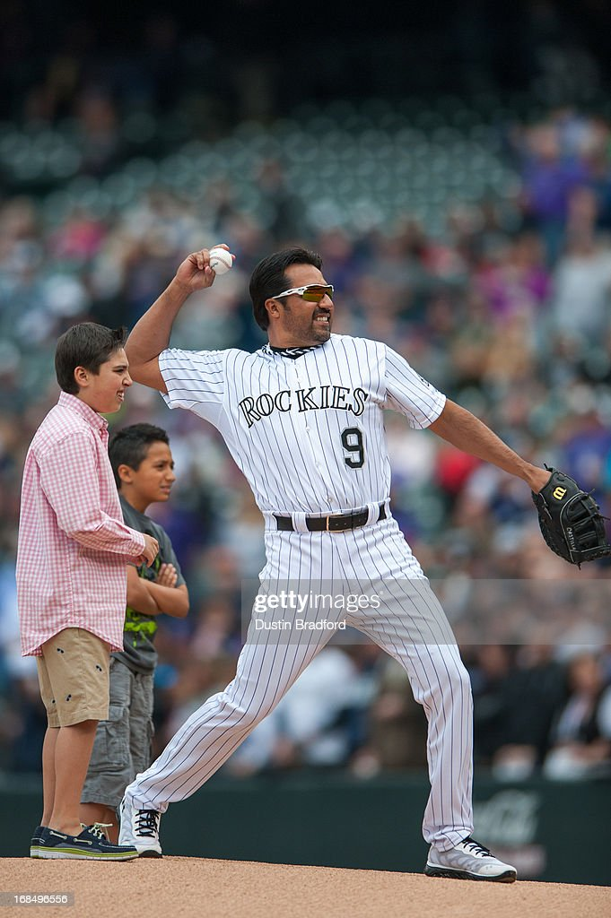 Vinny Castilla of the Colorado Rockies stands on to the field with two of his sons to throw out the ceremonial first pitch before a game against the...