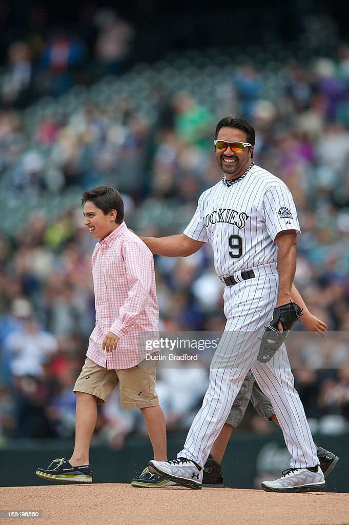 Vinny Castilla #9 of the Colorado Rockies stands on to the field with two of his sons to throw out the ceremonial first pitch before a game against the Tampa Bay Rays on a day where bobble head dolls with his likeness were given out to fans at Coors Field on May 5, 2013 in Denver, Colorado.
