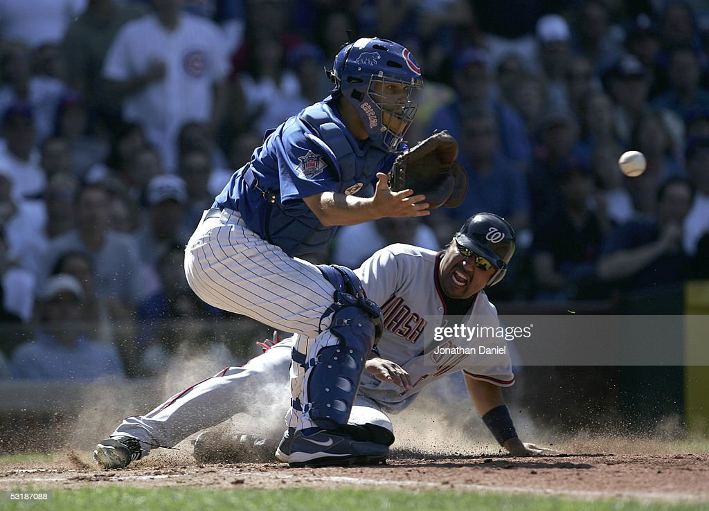 Vinny Castilla of the Washington Nationals slides into home to score a run in the fourth inning before Michael Barrett of the Chicago Cubs can catch...