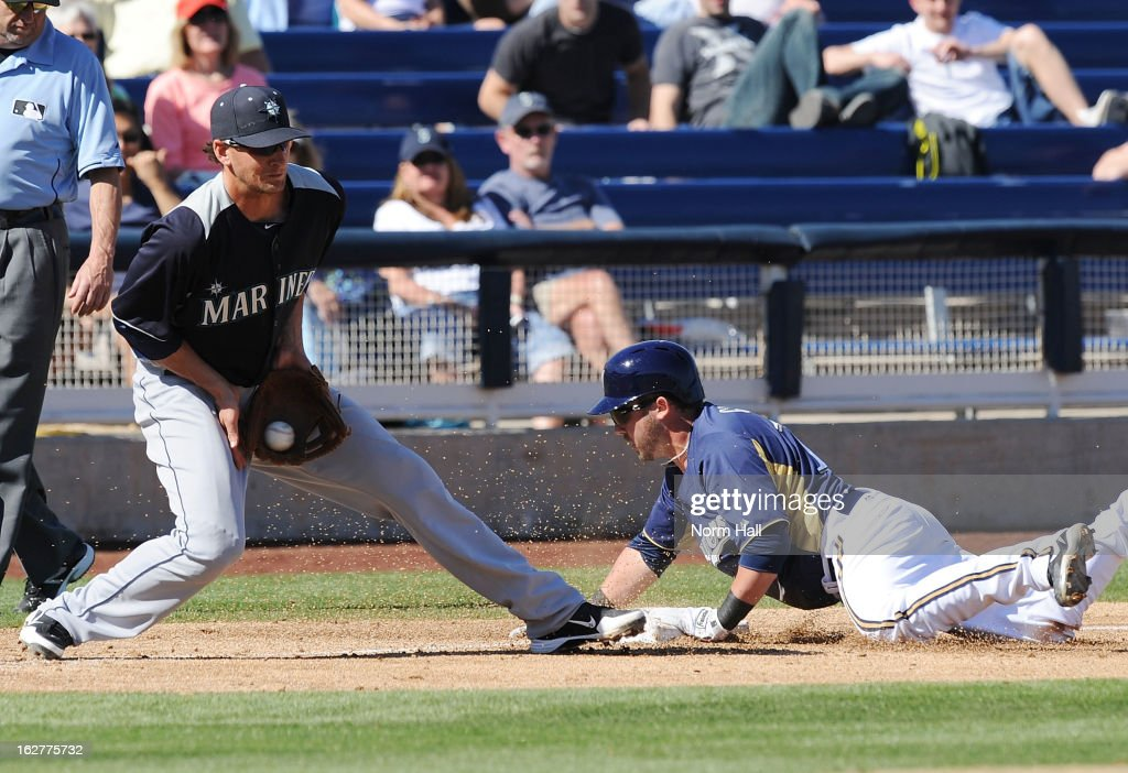 Vinny Catricala of the Seattle Mariners catches a throw as Caleb Gindl of the Milwaukee Brewers slides into third base at Maryvale Baseball Park on...