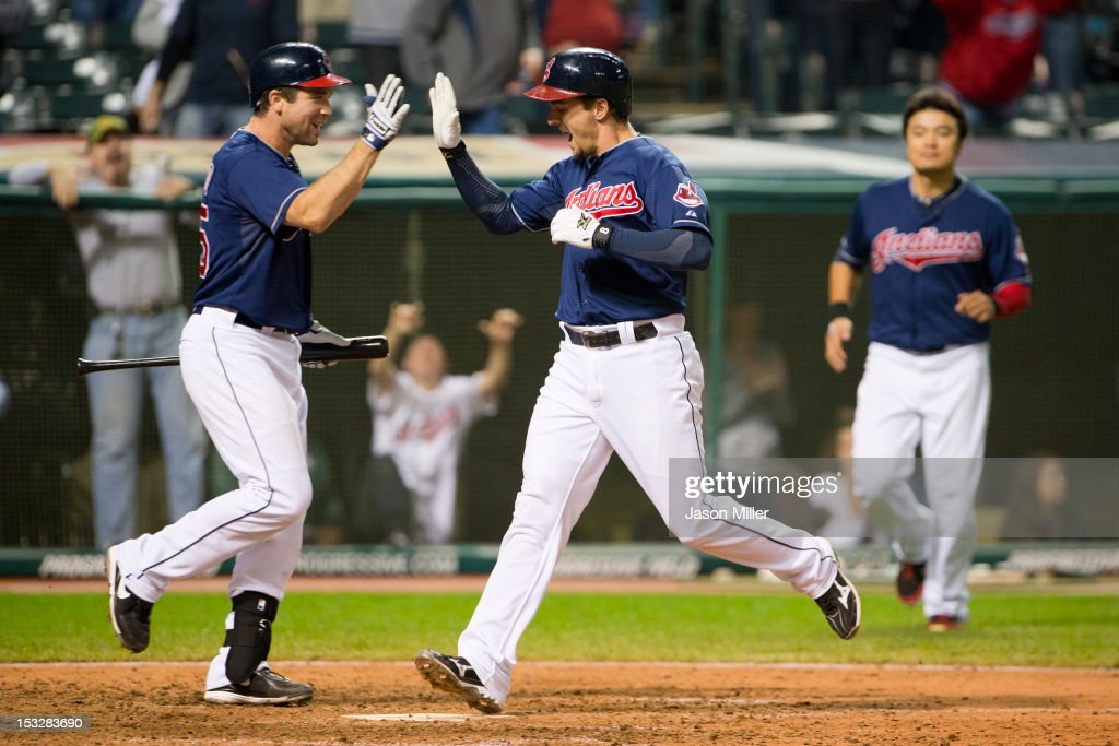 Vinny Rottino #25 celebrates with Lonnie Chisenhall #8 of the Cleveland Indians who scores the winning run off a single to left by Jason Donald #16 against the Chicago White Sox during the twelfth inning at Progressive Field on October 2, 2012 in Cleveland, Ohio. The Indians defeated the White Sox 4-3.
