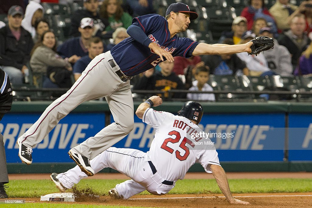 Vinny Rottino #25 of the Cleveland Indians is safe at third as third baseman <a gi-track='captionPersonalityLinkClicked' href=/galleries/search?phrase=Trevor+Plouffe&family=editorial&specificpeople=5722348 ng-click='$event.stopPropagation()'>Trevor Plouffe</a> #24 of the Minnesota Twins dives to catch a wide throw during the third inning at Progressive Field on September 19, 2012 in Cleveland, Ohio.
