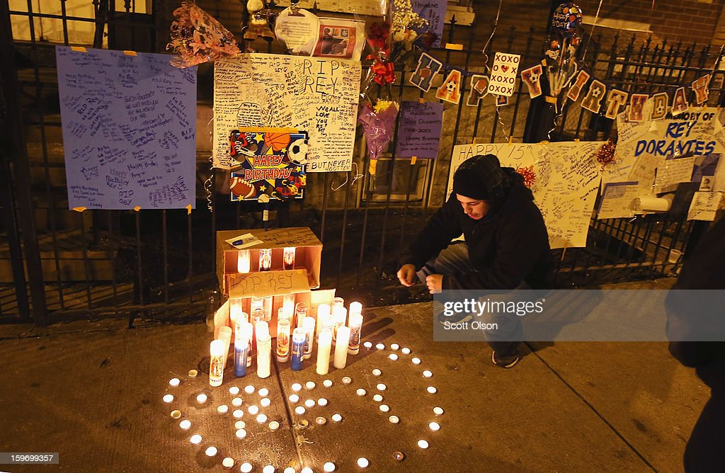 Vinny Tenev lights candles at a memorial for his stepbrother Rey Dorantes outside his home on what would have been Rey's 15th birthday on January 15, 2013 in Chicago, Illinois. Dorantes died after being shot 6 times while he was sitting on the front porch of the home on January 11. Dorantes' murder was the 21st homicide recorded in Chicago for 2013, a city which saw more than 500 homicides in 2012.
