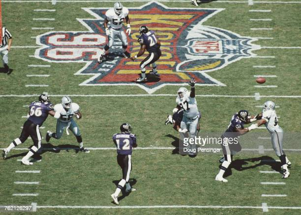 Vinny Testaverde Quarterback for the Baltimore Ravens throws a pass as Russell Maryland of the Oakland Raiders stretches to intercept the ball during...