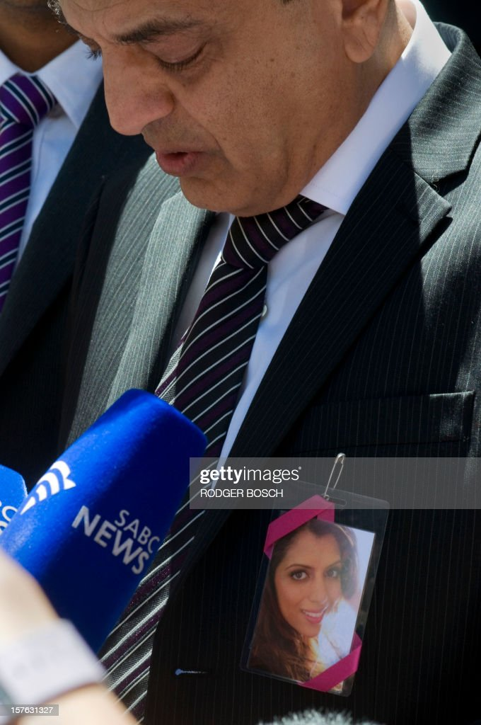 Vinod Hindocha father of murdered tourist, Anni Dewani, answers to journalists outside the High Court of Cape Town on December 5, 2012, wearing a photo of Annie on his chest. Xolile Mngeni the man convicted of firing the bullet that killed Anni was sentenced today to life imprisonment on the charges of murder, robbery and illegal possession of a firearm and ammunition in the Cape High Court. Dewani's husband, Shrien is fighting against being extradited from the UK to South Africa, allegedly for masterminding his wife's murder on November 13, 2011 in a poor township on the outskirts of Cape Town.