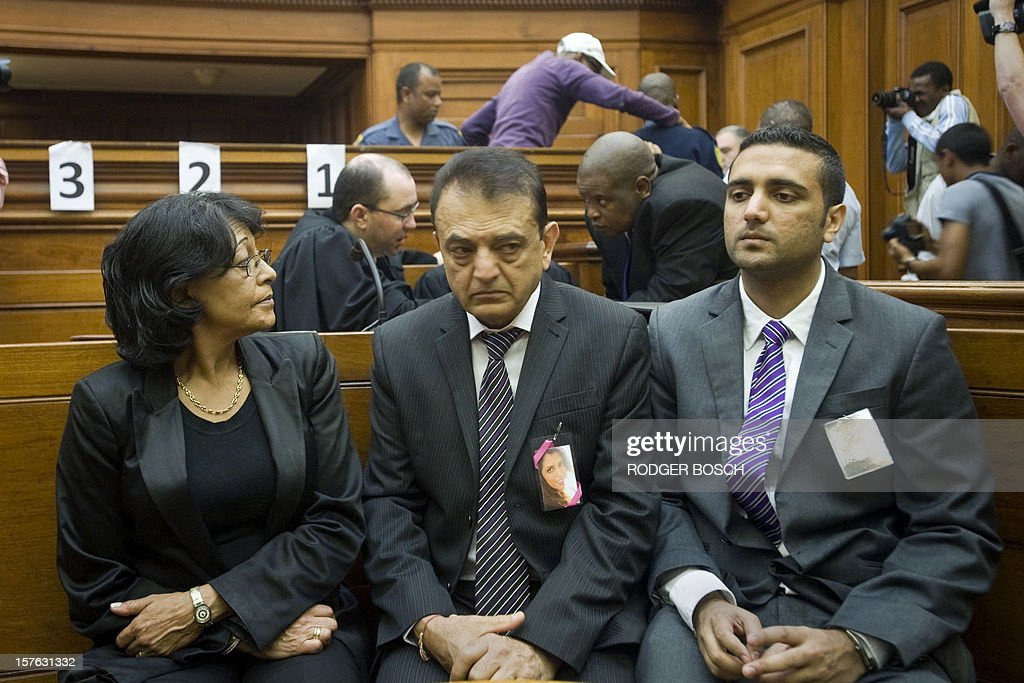 Vinod Hindocha (C) father of murdered tourist, Anni Dewani, flanked by his son Anish and police officer Louise Smit, sits in the High Court of Cape Town on December 5, 2012. Xolile Mngeni the man convicted of firing the bullet that killed Anni was sentenced today to life imprisonment on the charges of murder, robbery and illegal possession of a firearm and ammunition in the Cape High Court. Dewani's husband, Shrien is fighting against being extradited from the UK to South Africa, allegedly for masterminding his wife's murder on November 13, 2011 in a poor township on the outskirts of Cape Town. AFP PHOTO / RODGER BOSCH