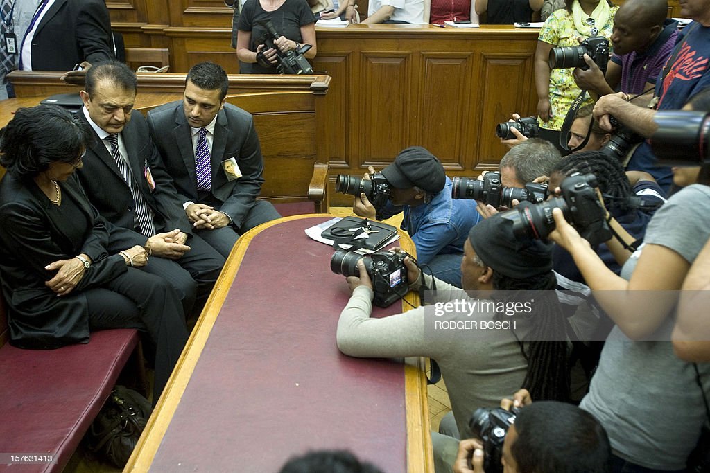 Vinod Hindocha (C) father of murdered tourist, Anni Dewani, flanked by his son Anish (R) and by police officer Louise Smit are pictured by photographers in the High Court of Cape Town on December 5, 2012. Xolile Mngeni the man convicted of firing the bullet that killed Anni was sentenced today to life imprisonment on the charges of murder, robbery and illegal possession of a firearm and ammunition in the Cape High Court. Dewani's husband, Shrien is fighting against being extradited from the UK to South Africa, allegedly for masterminding his wife's murder on November 13, 2011 in a poor township on the outskirts of Cape Town.