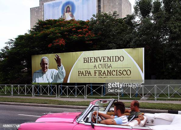 A vintage American car is driven past a poster of Pope Francis in Revolution Square on September 16 2015 in Havana Cuba Pope Francis is due to make a...