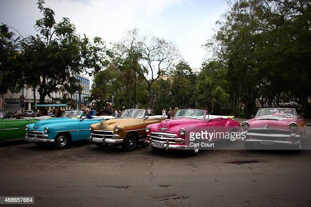 Vintage American cars being used as tourist taxis are parked alongside each other as drivers wait for customers on September 16 2015 in Havana Cuba...