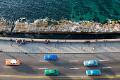 Vintage American cars speeding along the Malecon in Havana, Cuba, motion blur, Caribbean Sea is visible in the background, 50 megapixel image.