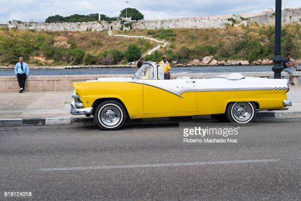 Vintage American cars used as tourist taxis in Havana This yellow and white convertible is parked on 'El 'Malecon' The driver leans on the wall of...