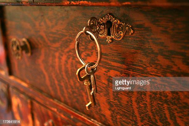 Vintage antique keys on the lock of a red wooden box