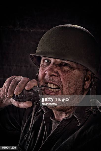Vintage Army Soldier pulling pin on hand grenade with teeth