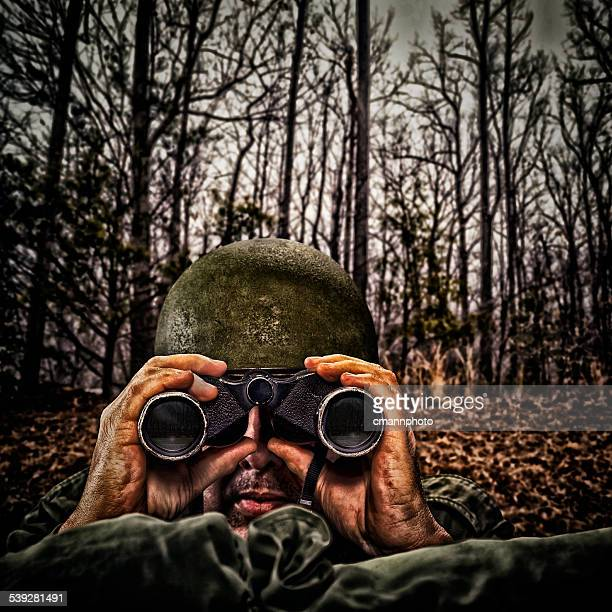 Vintage Army Soldier with binoculars in a fox hole