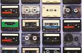 Retro audio cassette tapes on blue background. Top view on vintage media devices, copy space on labels, flat lay