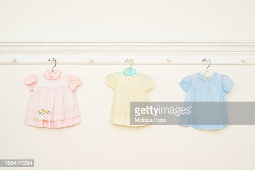 Vintage baby dresses hanging on a wall