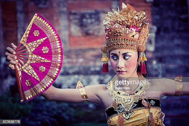 Vintage Bali performing dancer in a temple with fan