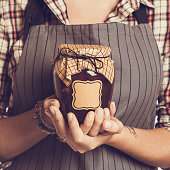 Vintage Bank peach jam in the hands of women. Close-up
