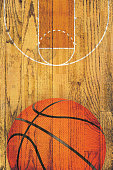 A basketball and court painted over a vintage hardwood floor background.