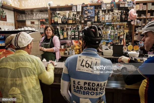 Vintage bicylcles enthusiasts drink a coffee before the start of the 21st edition of the 'L'Eroica of Gaiole in Chianti' bike ride at 500 pm on...