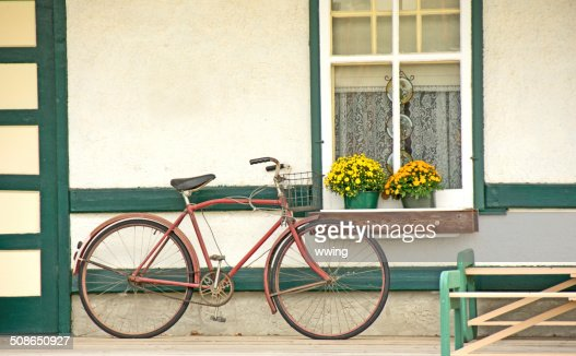 vintage bike resting against wall of home near a window : Stock Photo